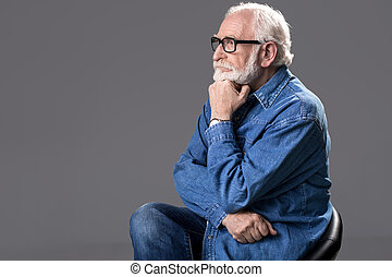 Thoughtful old man resting on chair - Profile of meditative...