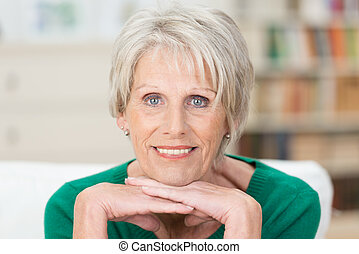 Thoughtful attractive female pensioner resting her chin on her hands looking intently at the camera with a quiet smile