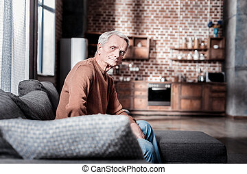 Thoughtful pensioner sitting at home