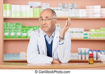 Thoughtful pharmacist standing over the drugstore background