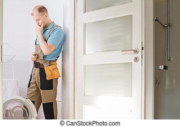 Thoughtful plumber repairing washing machine