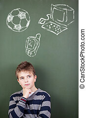 Thoughtful preadolescent student standing against chalkboard with soccer ball; mobile phone and computer drawn on it