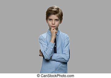 Thoughtful preteen boy on gray background.