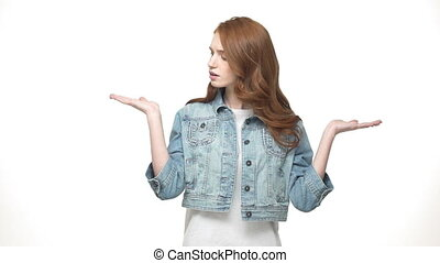 Thoughtful pretty redheaded woman present hand on side and hard to choose while standing isolated over white background
