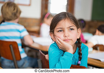 Thoughtful pupil sitting at her desk at the elementary ...