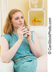 Thoughtful redhead sitting on the couch and holding mug