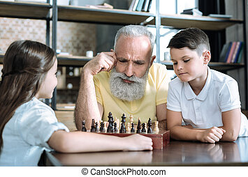 Thoughtful retired man playing chess with grandchildren
