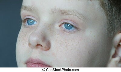 Thoughtful sad blue eyes of blond boy teenager with red...