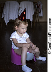 thoughtful sad child sitting on a potty