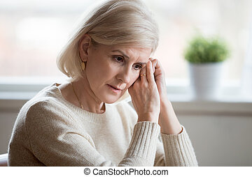 Thoughtful sad middle aged woman feeling blue thinking of anxiet