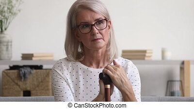 Thoughtful sad pensive old mature woman holding cane stick sit alone on sofa, upset depressed lonely senior retired grandmother thinking of loneliness health problems disease feel hopeless at home