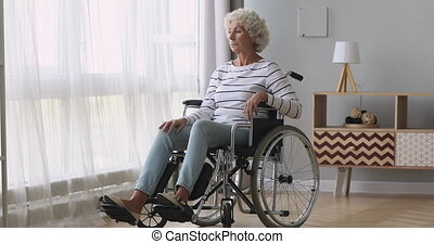 Thoughtful sad old woman sit on wheelchair alone at home