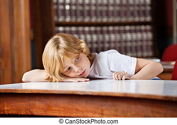 Thoughtful Schoolboy Leaning On Table In Library