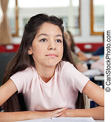 Thoughtful Schoolgirl Looking Away While Sitting At Desk
