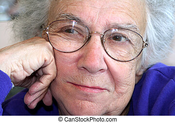 Closeup of a senior citizen woman with a thoughtful expression.