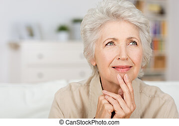 Thoughtful senior lady sitting at home with her fingers to ...