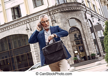 Thoughtful senior man in casual suit checking the time while standing outdoors