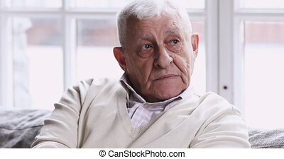 Unhappy lonely thoughtful elder senior man sit alone on sofa with hands folded look away think of solitude problem, sad old grandfather feel anxiety suffer from memory loss wait for support concept