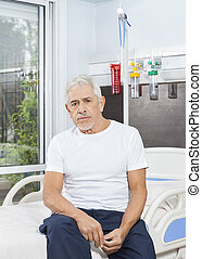 Thoughtful Senior Man Sitting On Bed At Rehab Center
