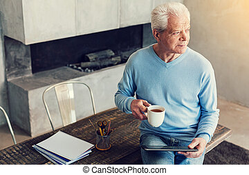 Thoughtful senior man sitting with a cup and a tablet