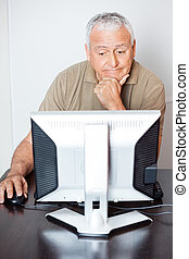 Thoughtful Senior Man Using Computer In Classroom