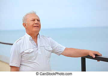thoughtful senior on veranda near seacoast, looking afar