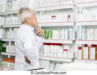 Thoughtful Senior Pharmacist Looking At Shelves