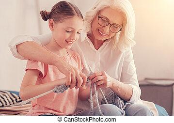 Thoughtful senior woman teaching granddaughter knitting