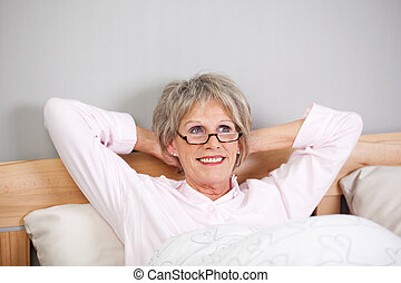 Thoughtful Senior Woman With Hands Behind Head In Bed -...
