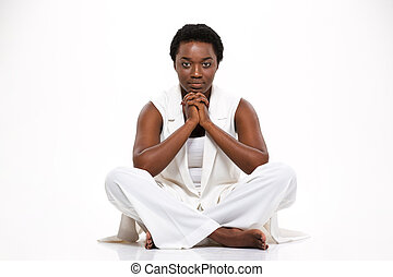 Thoughtful serious african american young woman sitting with legs crossed