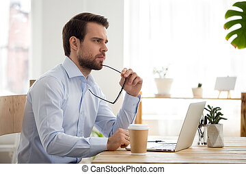 Thoughtful serious businessman lost in thoughts at work with laptop