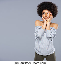 Thoughtful sexy beautiful young African American woman in a stylish off the shoulder top standing with her hands to her face staring pensively into the air, with copyspace