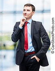 Thoughtful smiling boss in business suit in office
