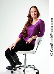 Thoughtful smiling woman sitting on the chair over gray background