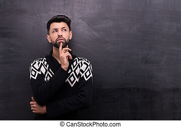 Thoughtful stylish man on blank chalkboard background