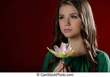 Thoughtful teenage girl. Pretty teenage girl holding a flower and looking away while isolated on red