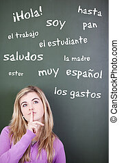 Thoughtful teenage girl with finger on lips looking up against Spanish words written on blackboard