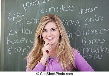 Thoughtful teenage girl with hand on chin against Spanish words written on blackboard