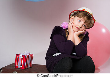 Thoughtful teenager in a hat sitting on a suitcase