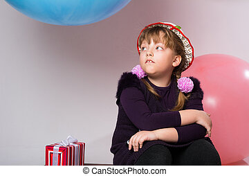 Thoughtful teenager in a hat sitting with a gift