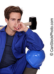 Thoughtful tradesman holding a mallet