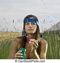 thoughtful woman blowing soap bubbles - thoughtful young...