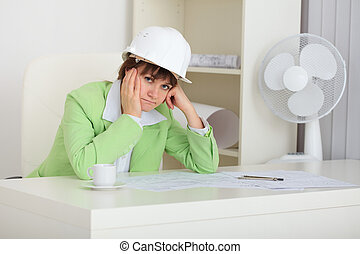 Thoughtful woman - builder in helmet