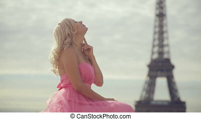 Thoughtful woman dressed in festive pink strapless dress near the Eiffel Tower in Paris