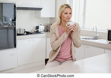 Thoughtful woman drinking coffee in kitchen