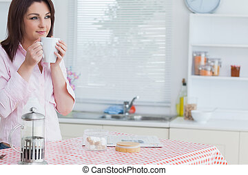 Thoughtful woman drinking coffee in the kitchen