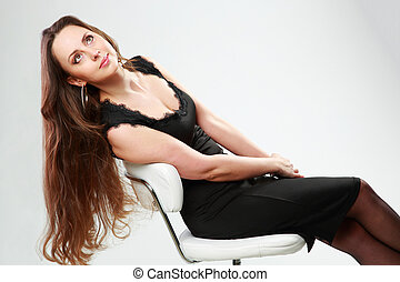 Thoughtful woman in black dress sitting on the office chair over gray background