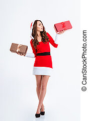 Thoughtful woman in santa claus cloth holding two gift boxes