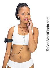 Thoughtful woman in sportswear listening to music
