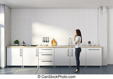 Thoughtful woman in white kitchen